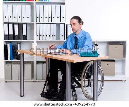 disabled business man in wheelchair is writing - stock photo