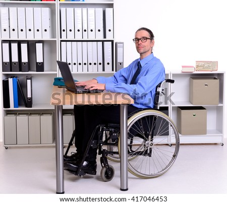 disabled business man in wheelchair looking in to the camera - stock photo