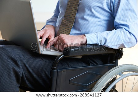 Disabled Businessman In Wheelchair Using Laptop - stock photo