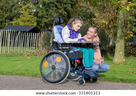 Disabled child in wheelchair relaxing outside together  with a care assistant / Working with disability - stock photo