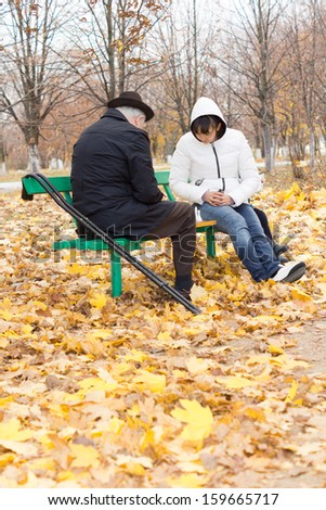 Disabled elderly man with crutches and an attractive younger woman playing chess sitting together on a wooden park bench wrapped up warmly against the cold autumn weather - stock photo