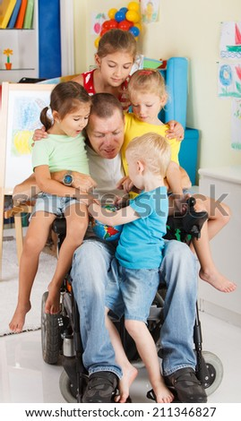 Disabled Father play with his little son and three daughters - stock photo
