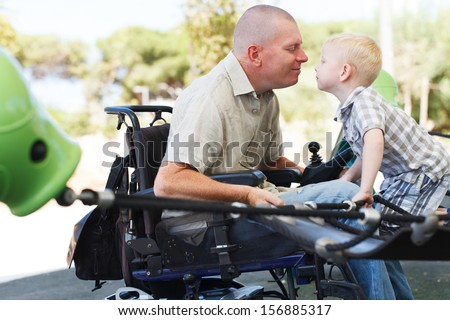 Disabled Father play with his little son on the playground - stock photo