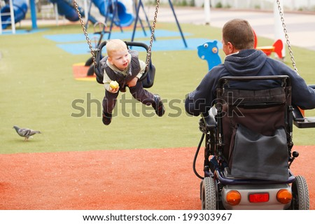 Disabled Father play with his little son on the playground. - stock photo