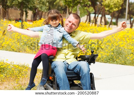 Disabled Father showing freedom with his little daughter. - stock photo