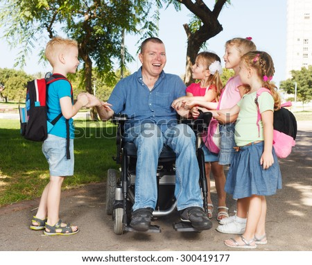 Disabled father with children showing unity - stock photo