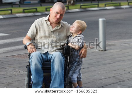 Disabled Father with his little son on the sidewalk - stock photo