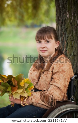 disabled girl in wheelchair in the autumn park - stock photo