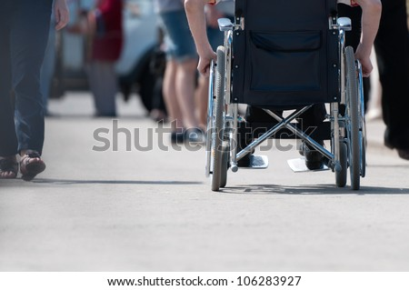 Disabled (handicapped) person on wheeled chair among people without disabilities. Place for copy. - stock photo