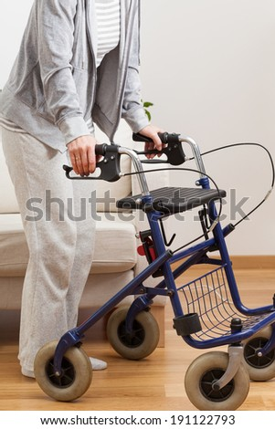 Disabled lady during walking with walker, vertical - stock photo