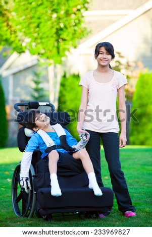 Disabled little boy in wheelchair with sister on grassy lawn outdoors - stock photo
