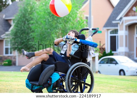 Disabled little boy playing ball in the park - stock photo