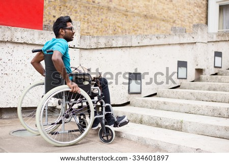 disabled man in a wheelchair waiting at the bottom of steps - stock photo