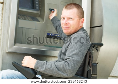 Disabled Man put her credit card at the ATM.  - stock photo