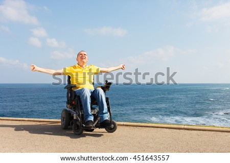 Disabled man sitting in wheelchair showing freedom. - stock photo