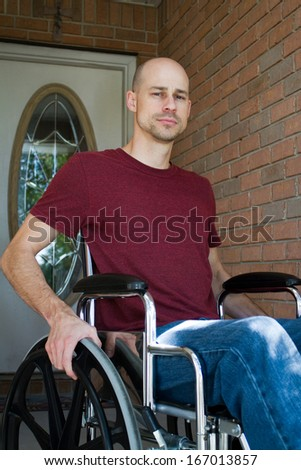 Disabled man suffering from an illness sits in his wheelchair in front of his home. - stock photo