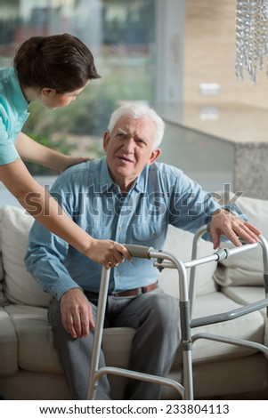 Disabled man using walking frame and helpful nurse - stock photo