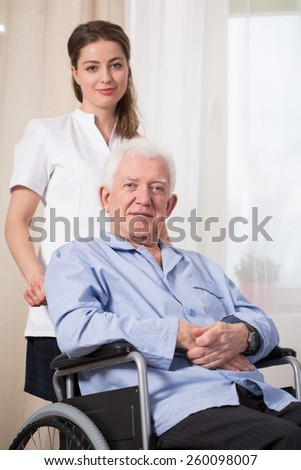 Disabled man using wheelchair at nursing home - stock photo