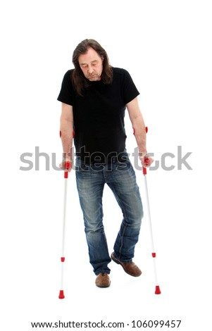 Disabled middle-aged man wearing jeans walking on crutches studio portrait isolated on white - stock photo