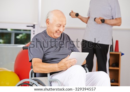 Disabled old man sitting in wheelchair with tablet PC in a nursing home - stock photo