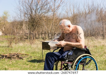 Disabled Old Man with No Shirt Sitting on his Wheelchair and Eating his Lunch at the Park Alone on a Very Sunny Day. - stock photo