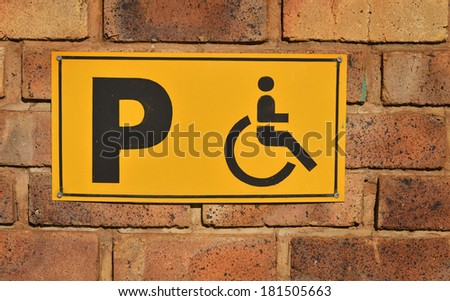 Disabled parking sign on a brick wall - stock photo