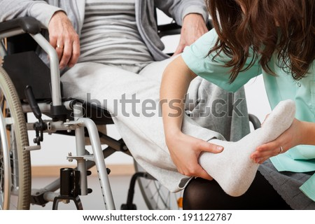 Disabled person during rehabilitation with her nurse - stock photo