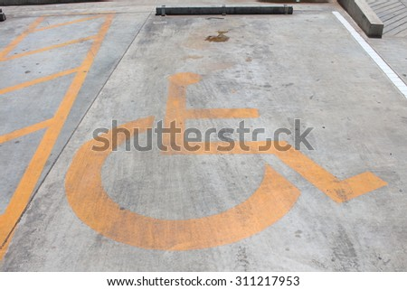 Disabled person parking place permit mark, traffic symbol on the cement - stock photo