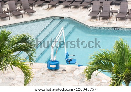 Disabled person pool lift meets ADA standards installed by swimming pool to lower people into water - stock photo