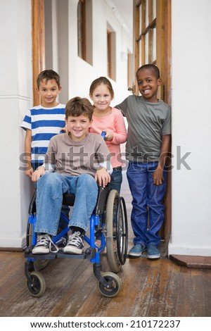 Disabled pupil with his friends in classroom at the elementary school - stock photo