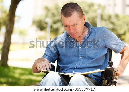 Disabled reading a book at the park - stock photo