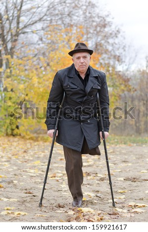 Disabled senior man on crutches determined to continue to enjoy a healthy active lifestyle enjoying a walk in an autumn park in his coat and hat - stock photo