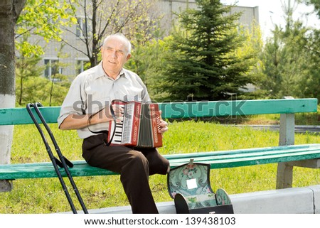 Disabled senior man with one leg amputated above the knee sitting on a park bench playing the accordion - stock photo
