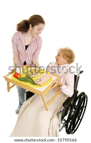 Disabled senior receives a home meal delivery from friendly teen volunteer.  Vertical view isolated on white. - stock photo