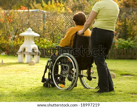 Disabled senior woman in a wheelchair - stock photo