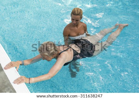 Disabled senior woman with therapist for aqua-gym reeducation - stock photo