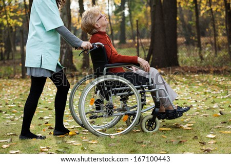 Disabled senior woman with young nurse walking at park - stock photo