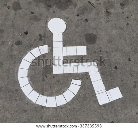 Disabled sign on floor in car parking - stock photo