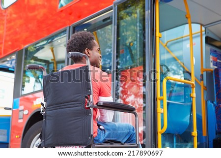 Disabled Woman In Wheelchair Boarding Bus - stock photo