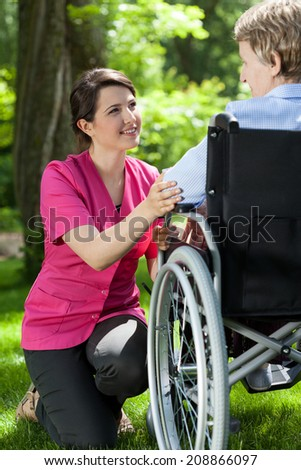Disabled woman resting in garden with nurse - stock photo