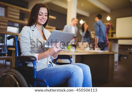 Disabled young businesswoman using digital tablet in creative office - stock photo