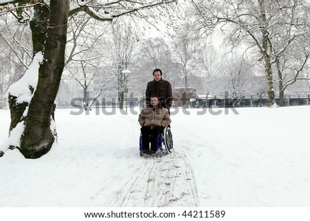 disabled young man in wheelchair with his friend at the park - stock photo