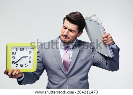 Disappointed businessman holding folders and clock over gray background - stock photo