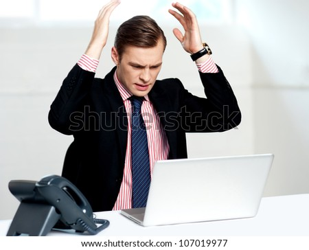 Disappointed businessman looking at laptop with hands above his head - stock photo