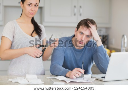Disappointed couple in the kitchen cutting credit card and looking at finances on laptop - stock photo