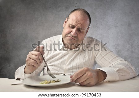 Disappointed fat man eating vegetables - stock photo