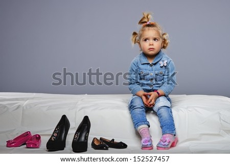 Disappointed little girl sitting on a bed with different shoes near  - stock photo