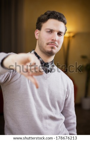 Disappointed or displeased young man doing thumb down sign. Indoors shot inside a house - stock photo