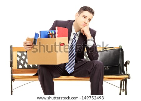 Disappointed redundant young man in a suit sitting on a bench with a box of belongings isolated on white background - stock photo