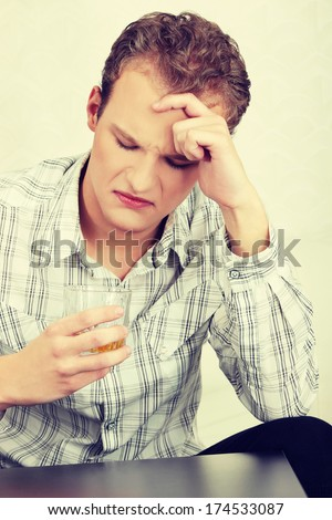 Disappointed, sad man sitting with alcohol drink (glass of whiskey). Young and lonely depressed man wearing bright, plaid shirt with his head down.  - stock photo